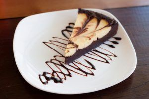 Fatia de cheesecake de brownie decorado com calda de chocolate