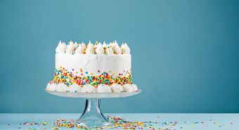 White,Birthday,Cake,With,Colorful,Sprinkles,Over,A,Blue,Background.