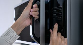 Woman's,Hands,Closing,The,Microwave,Oven,Door,And,Preparing,Food