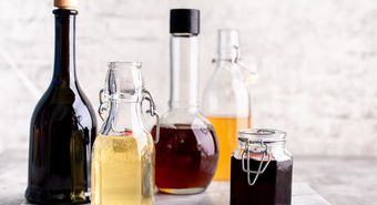 Original,Glass,Bottles,With,Different,Vinegar,On,A,Marble,Table